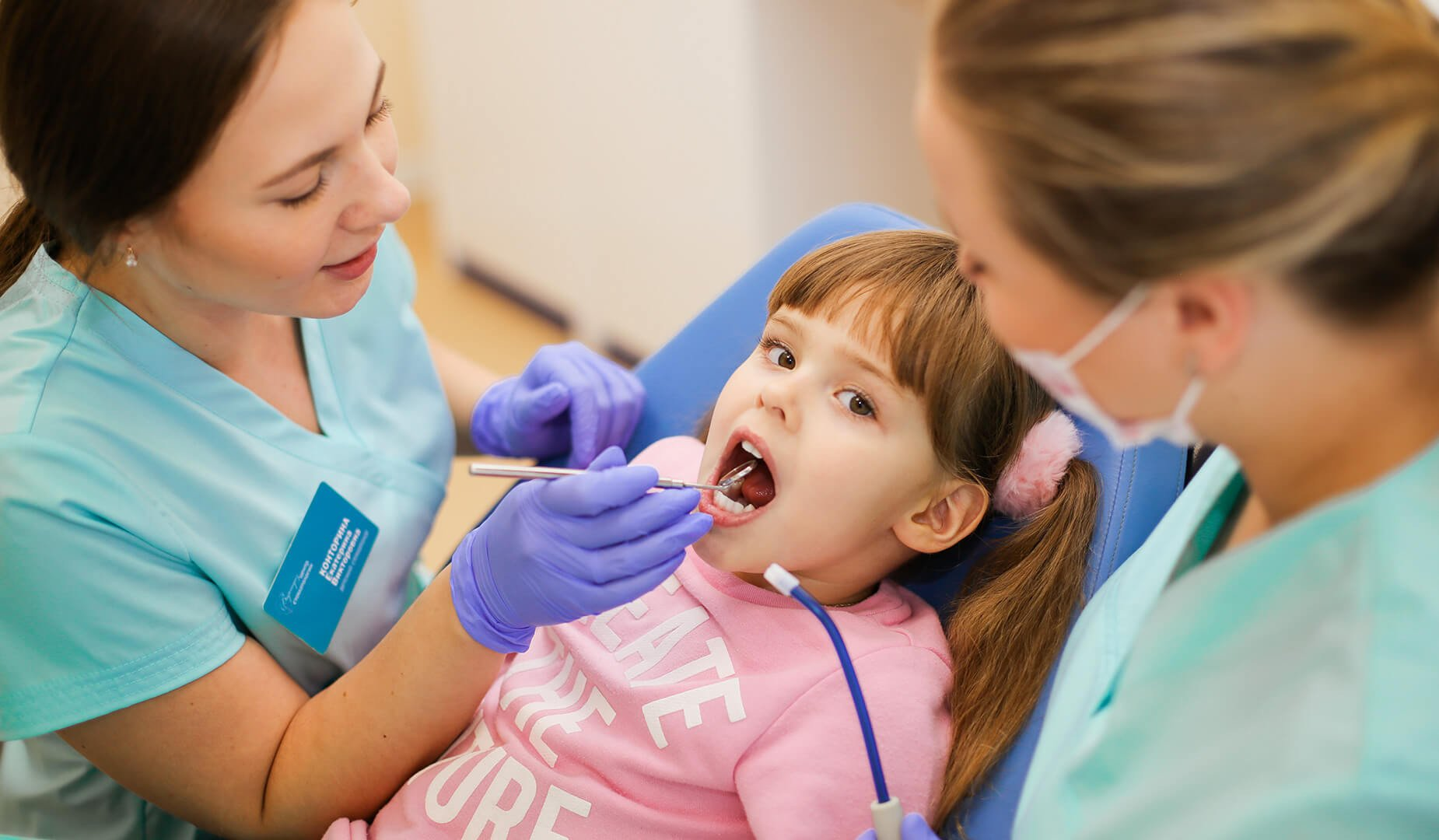 Осмотр маленькой пациентки в кресле у стоматолога