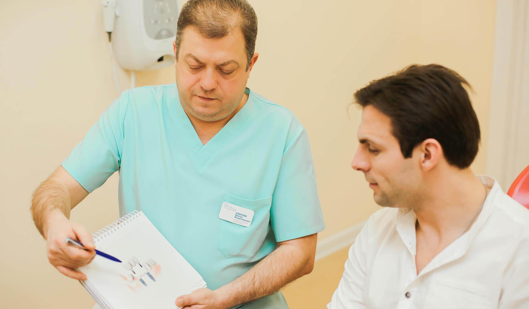 Врач показывает пациенту схему вживления импланта