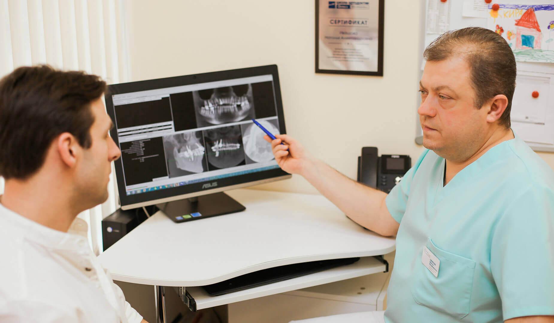 Врач показывает пациенту его снимок КТ на компьютере
