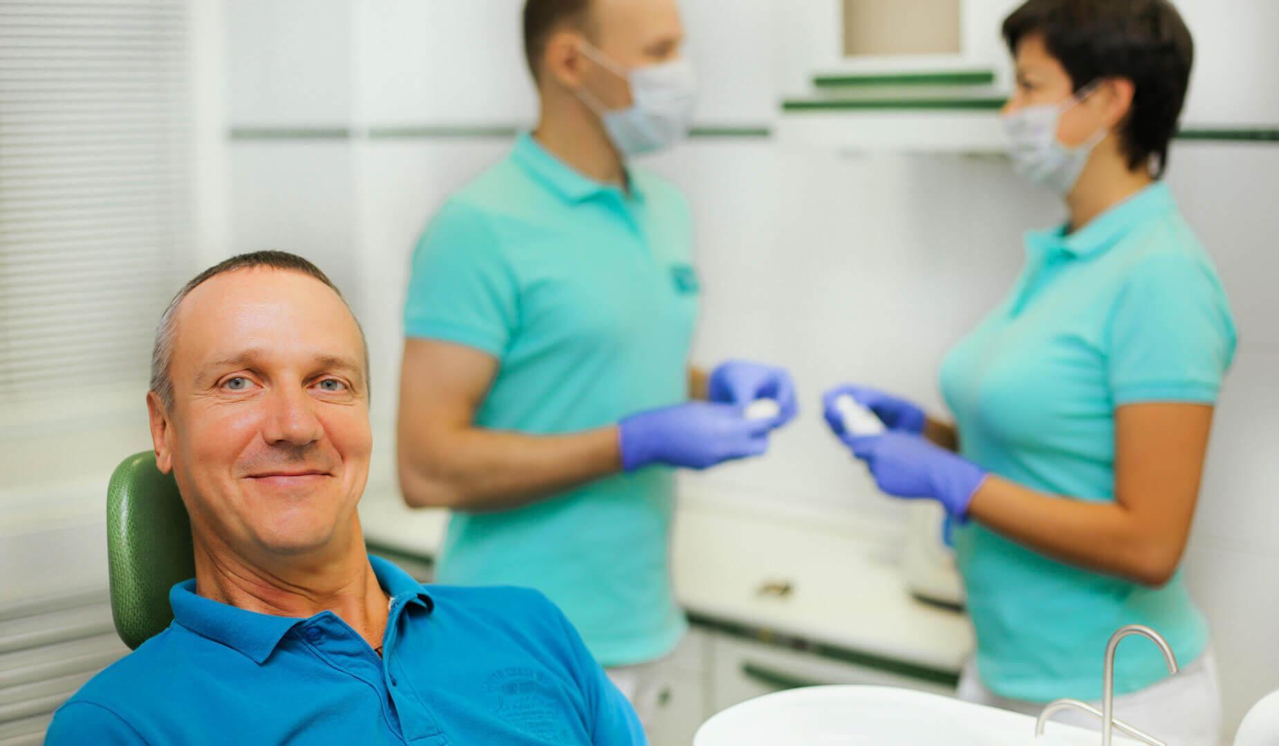 Пациент улыбается в кресле стоматолога
