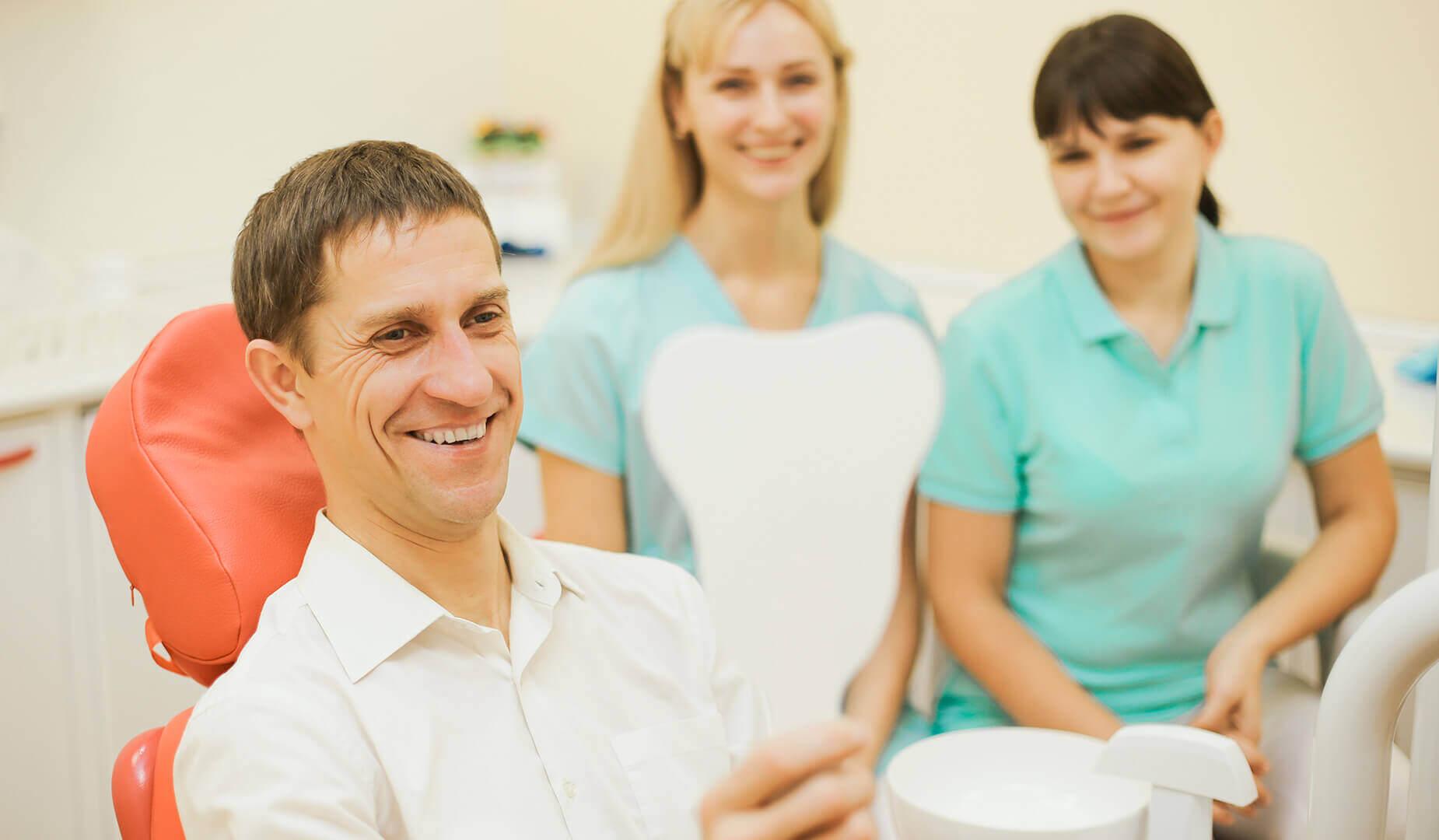 Пациент смотрит на свою новую красивую улыбку в зеркало