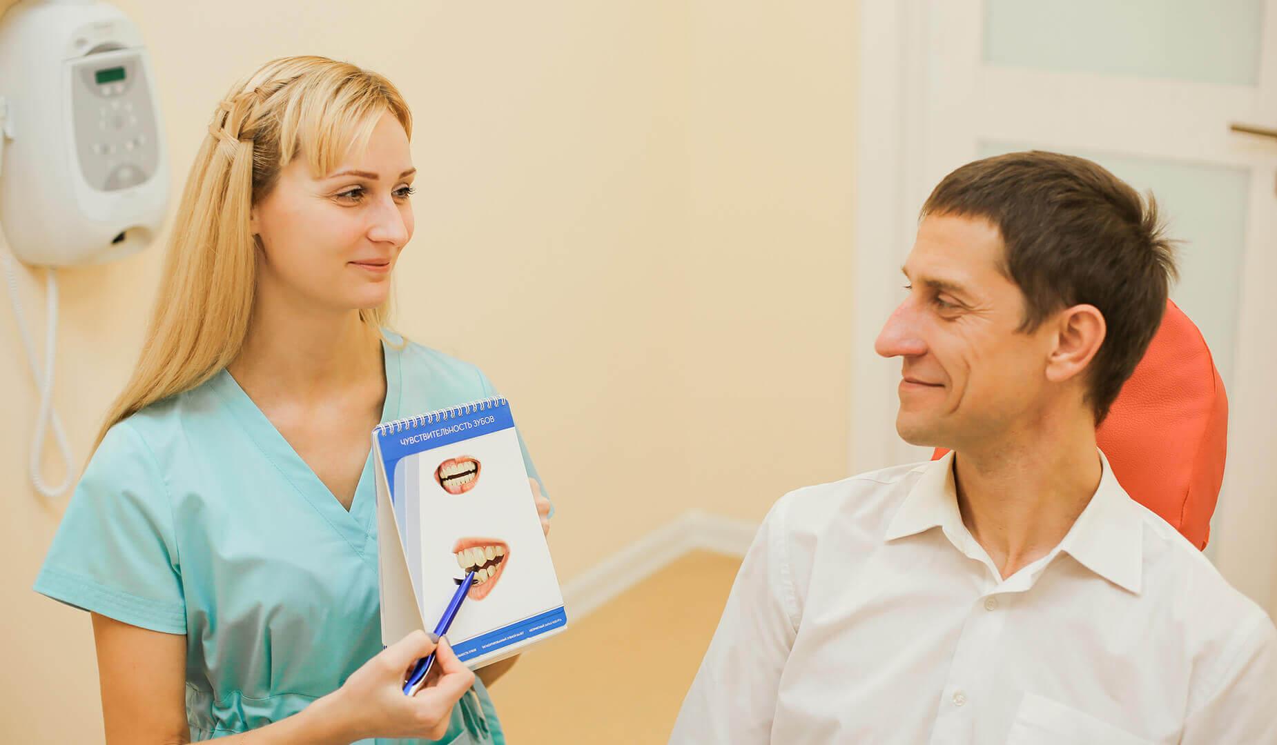 Врач наглядно рассказывает пациенту, как возникает кариес