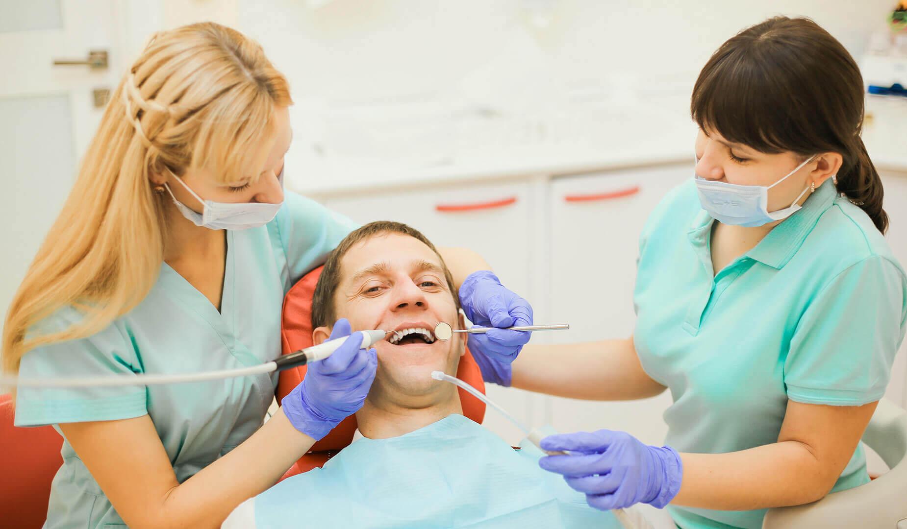 Пациенту удаляют зубной камень скайлером
