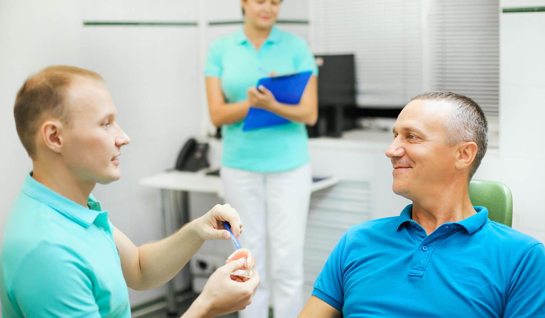 Врач показывает пациенту макет челюсти с установленным имплантом