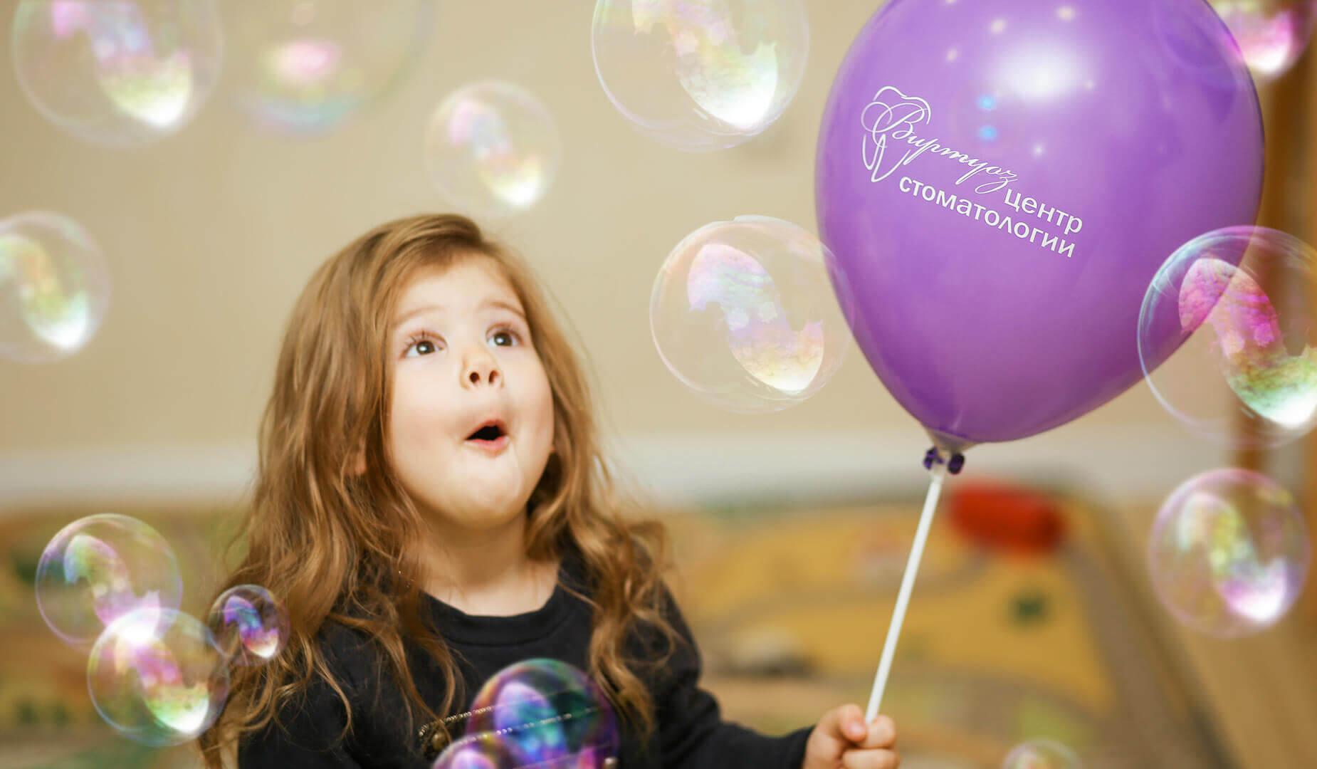 Девочка радуется мыльным пузырям и воздушному шару