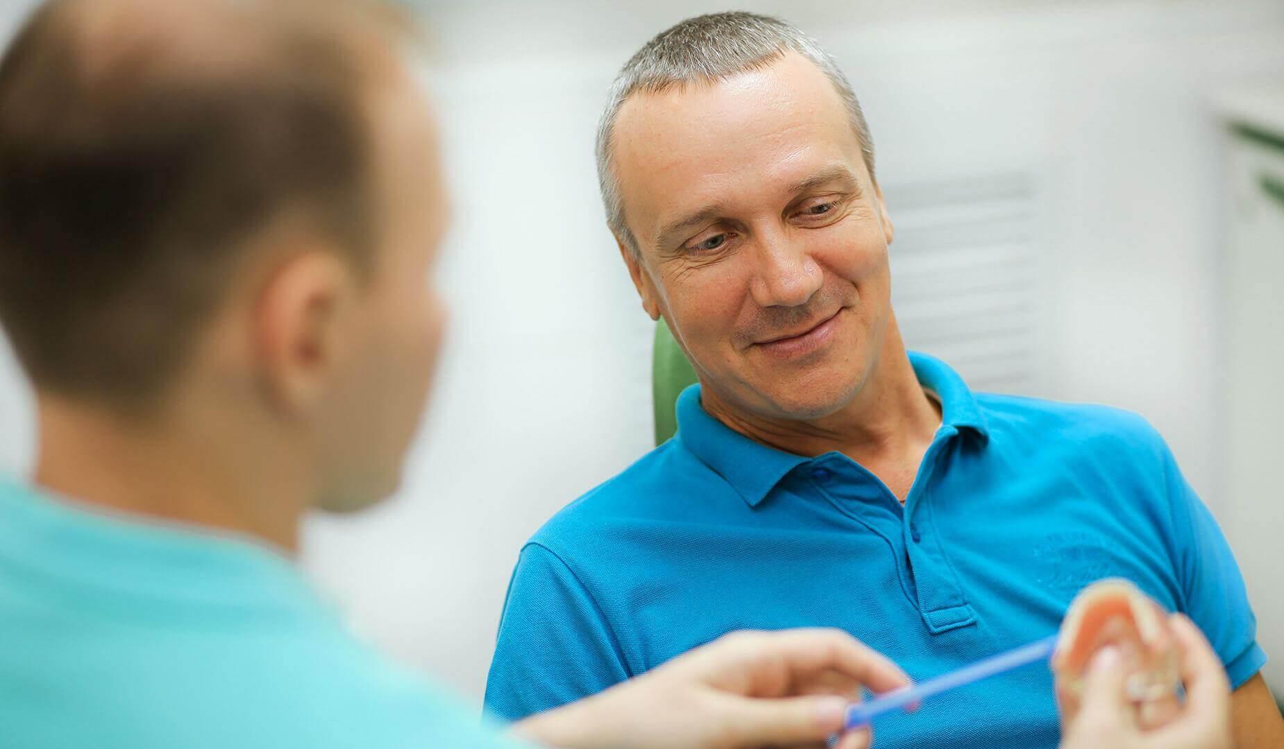 Врач показывает пациенту макет челюсти