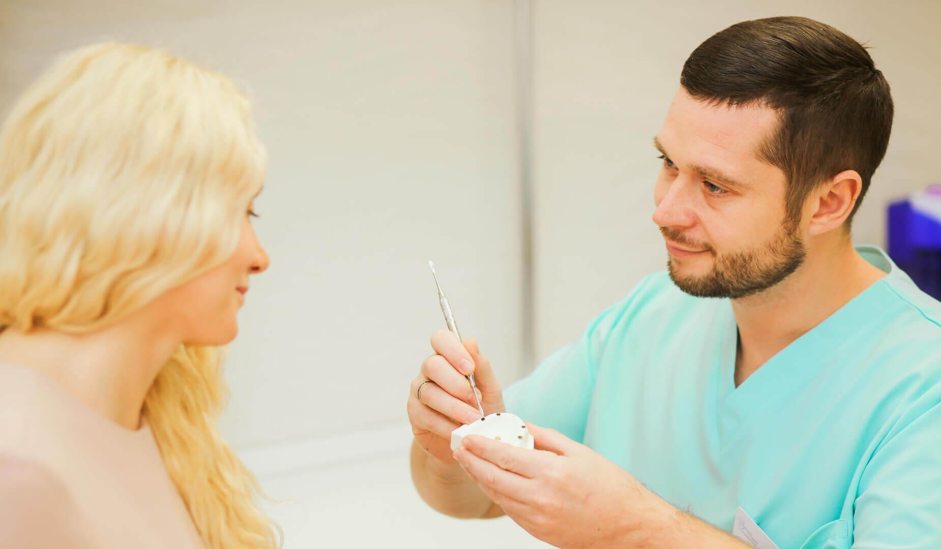 Врач поясняет пациентке особенности съёмных протезов