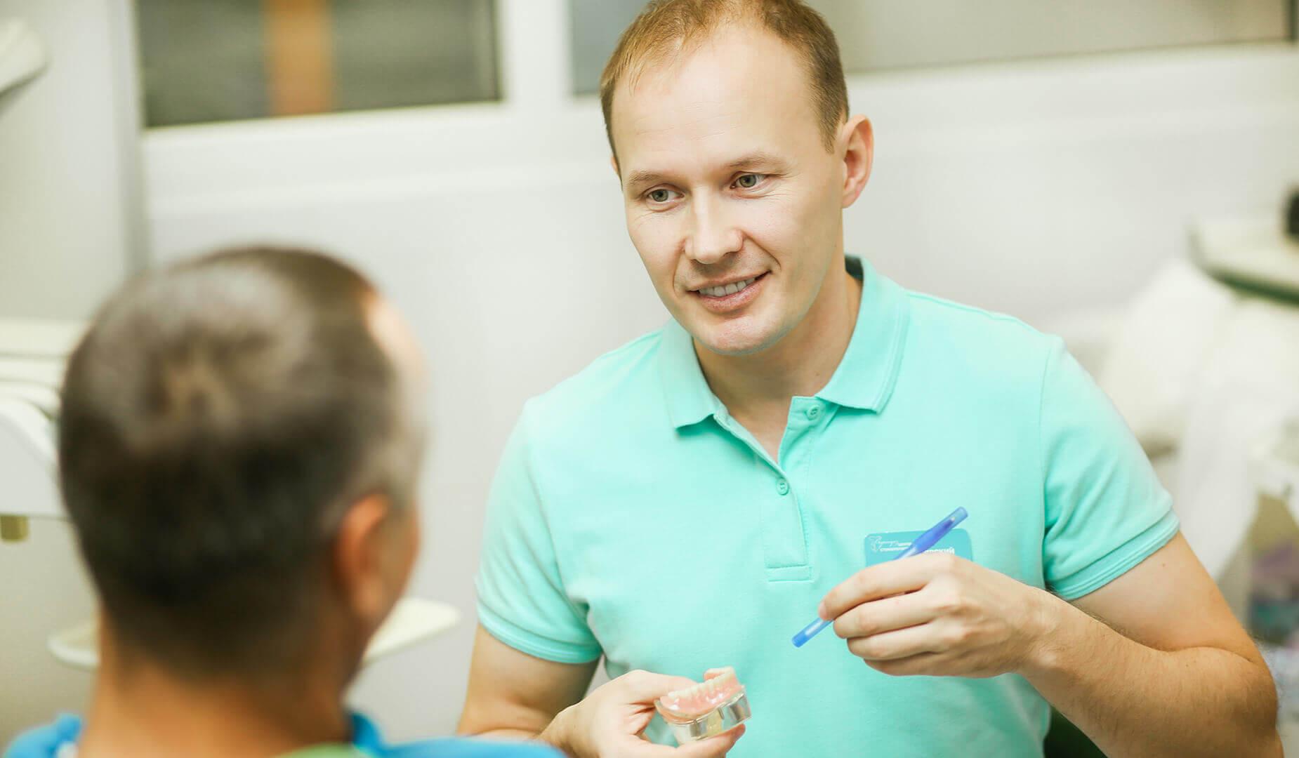 Врач рассказывает пациенту про имплантацию